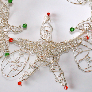 Silver wire has been twisted and twirled to create a sparking and delicate Christmas Wreath.